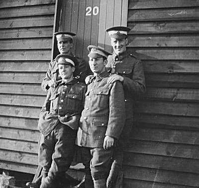 Flight Cadets at Denham in 1917 lean against one of the huts that made up the accomodation at the camp.